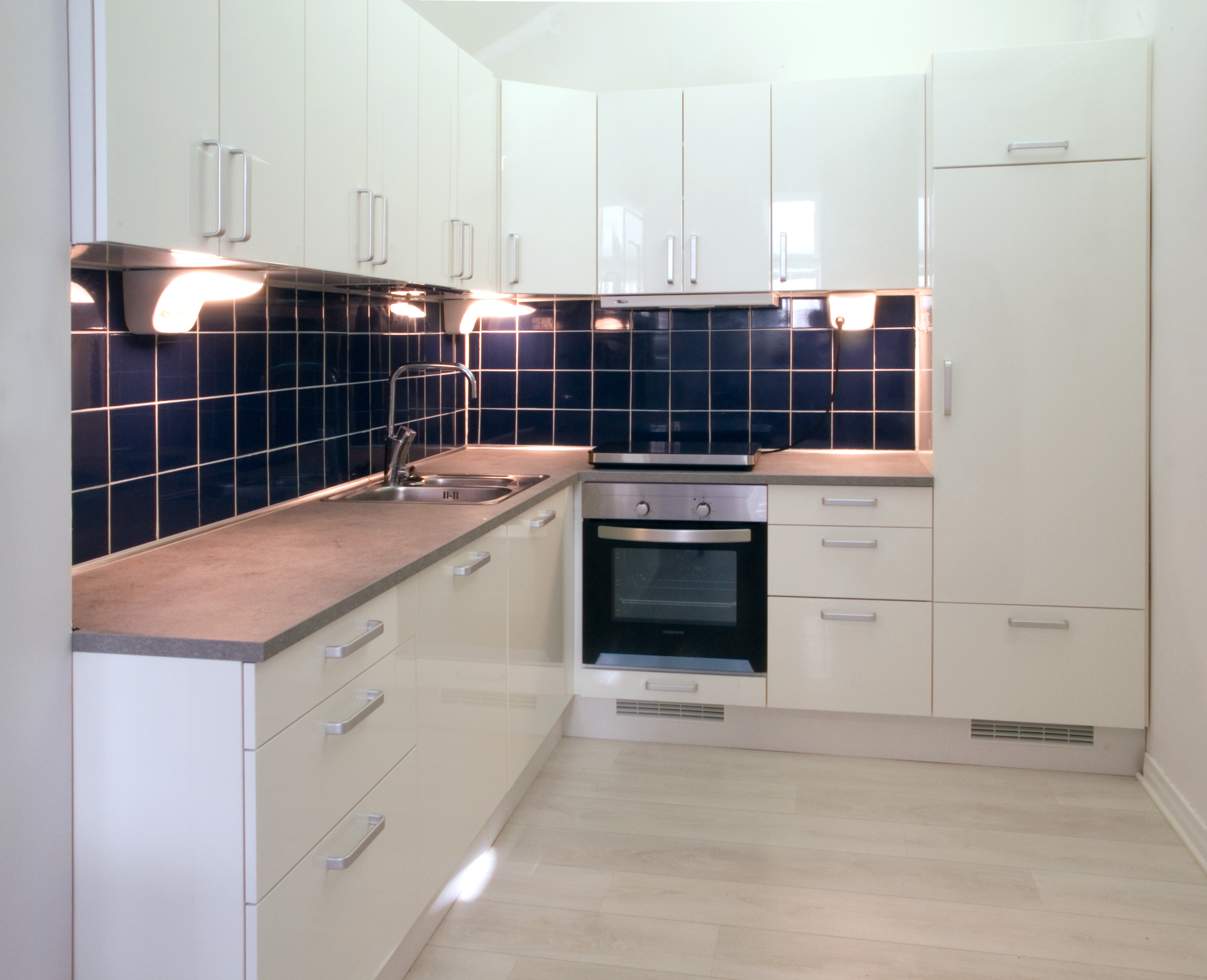 White Kitchen with Dark Blue Tiling photo - 1